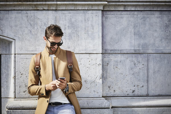 Smiling man in camel coat looking at mobile phone