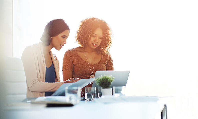 two women talking in an office setting looking at laptop