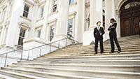 Zwei Personen in Anzügen, die auf den Stufen eines Regierungsgebäudes stehen.