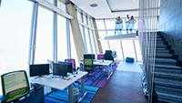 Ein offener, lichtdurchfluteter Bürobereich mit vielen Bildschirmen und sauberen Schreibtischen.