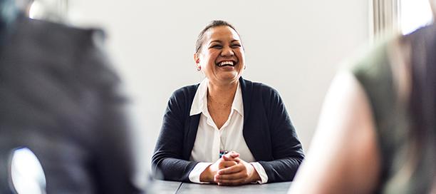 Eine lächelnde Frau, die an einem Office-Tisch sitzt.