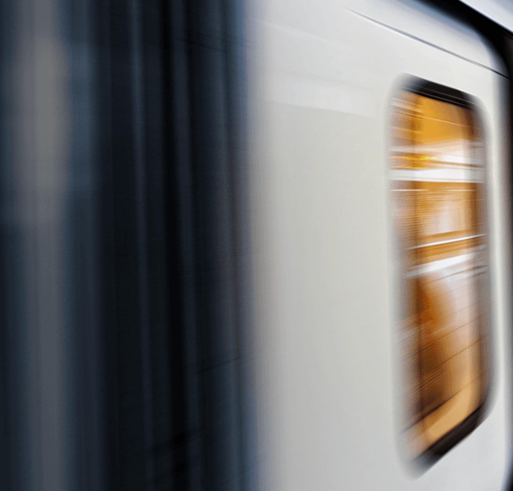 Ein Zug, der mit hoher Geschwindigkeit durch einen Bahnhof fährt.