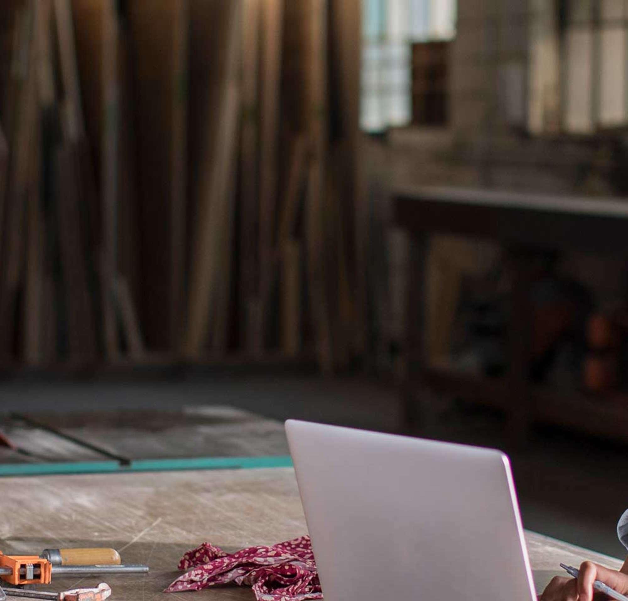 Junge Frau arbeitet von einem Laptop in ihrer Holzwerkstatt