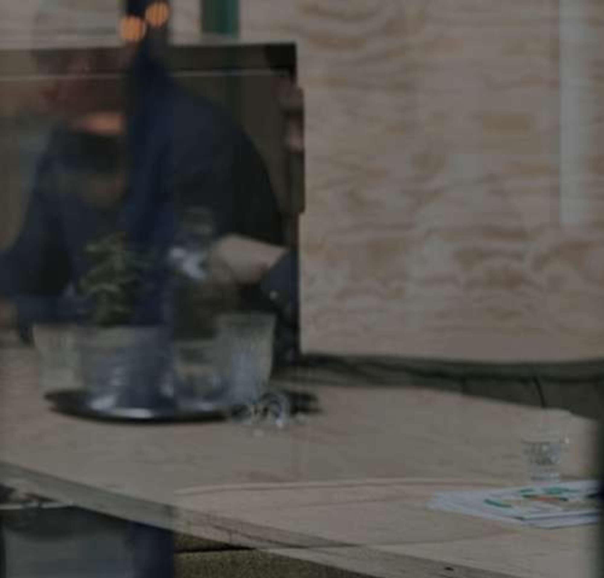 Frau mit Headset, die am Laptop arbeitet und ihr Telefon dabei trägt.