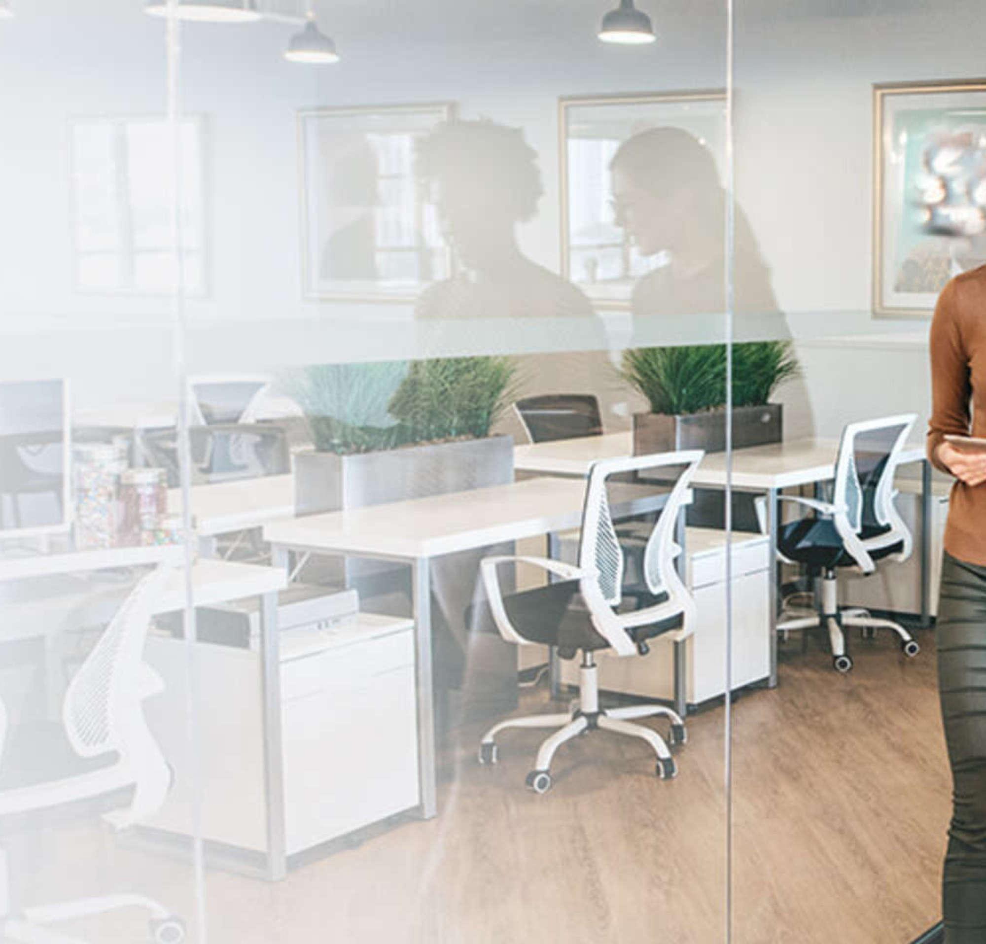 Zwei Frauen, die in einem Konferenzzimmer nebeneinander laufen und ein Dokument anschauen.