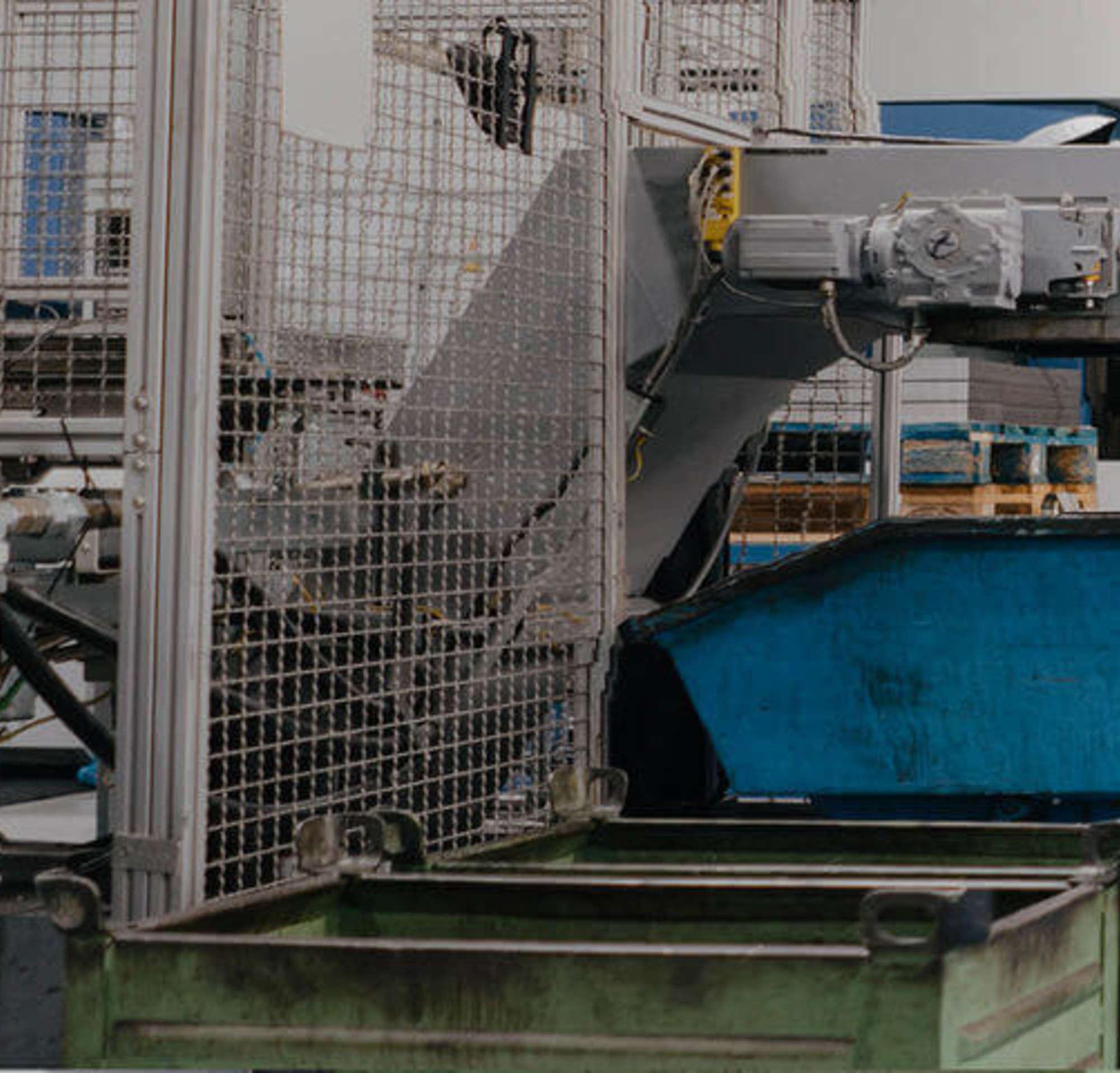 Ein Mann in einem Anzug, der mit einem Fabrikarbeiter durch eine Fabrik mit großen Maschinen geht.