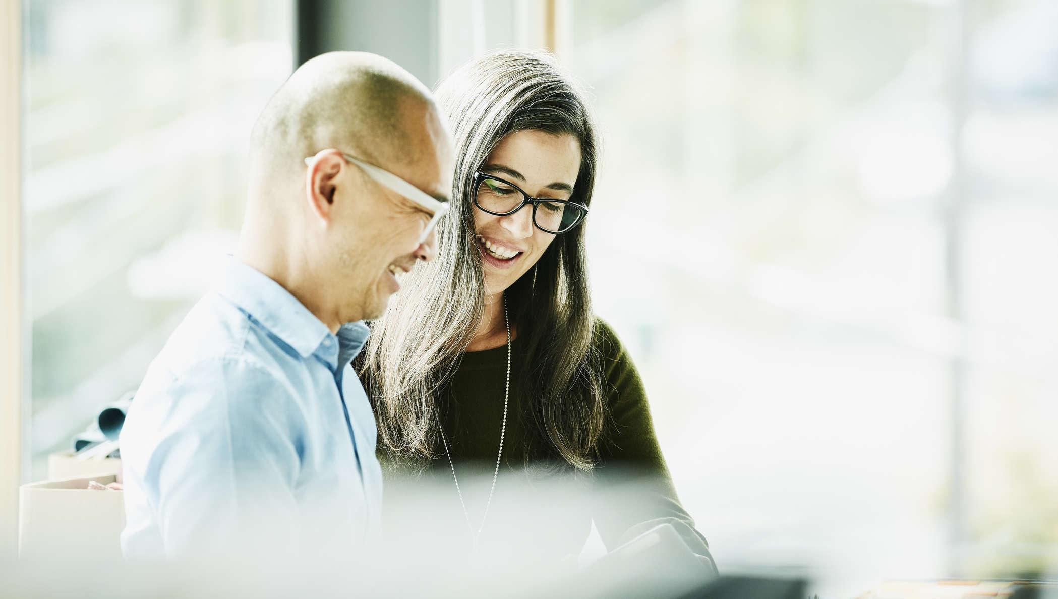 Ein Mann und eine Frau gucken auf ein iPad.