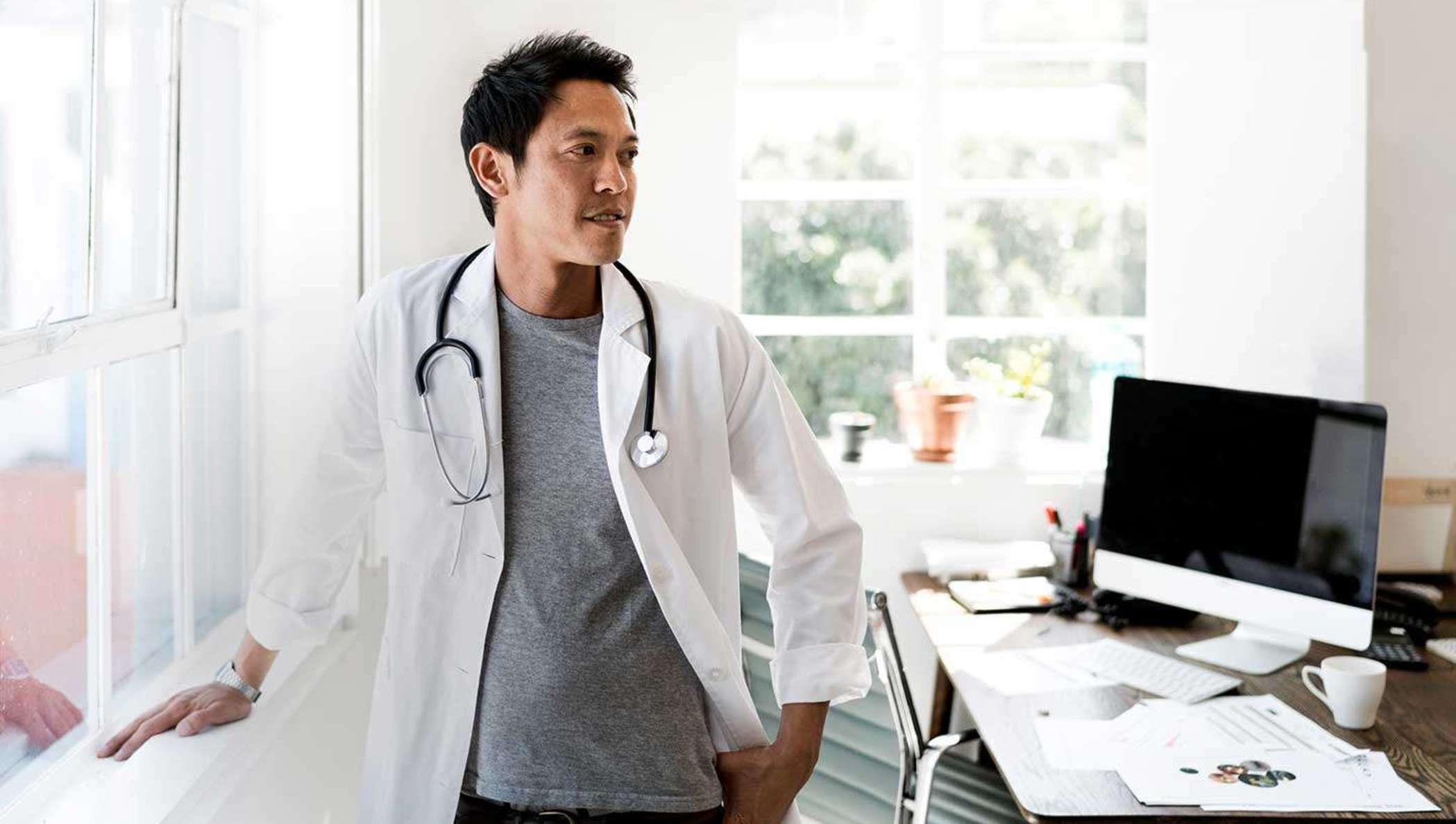 Ein Arzt neben einem Bürofenster, der an seinem Schreibtisch vorbei schaut.