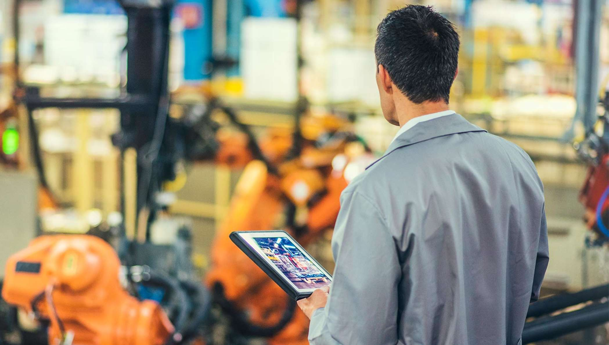 Ingenieur in einem grauen Mantel, der autonome Roboterarme betrachtet, während er ein Tablet hält.