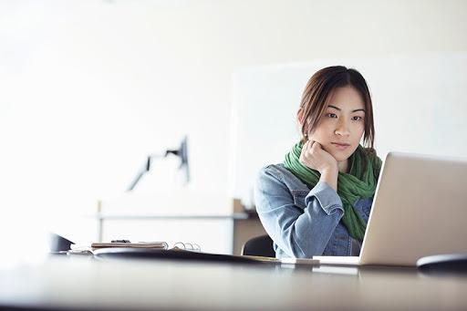 Frau, die auf Laptop guckt